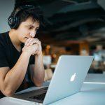 jeune homme concentré devant son ordinateur à la bibliothèque écoute un cours dans son casque