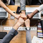 poings unis autour d'un projet ordinateur et classeurs sur la table