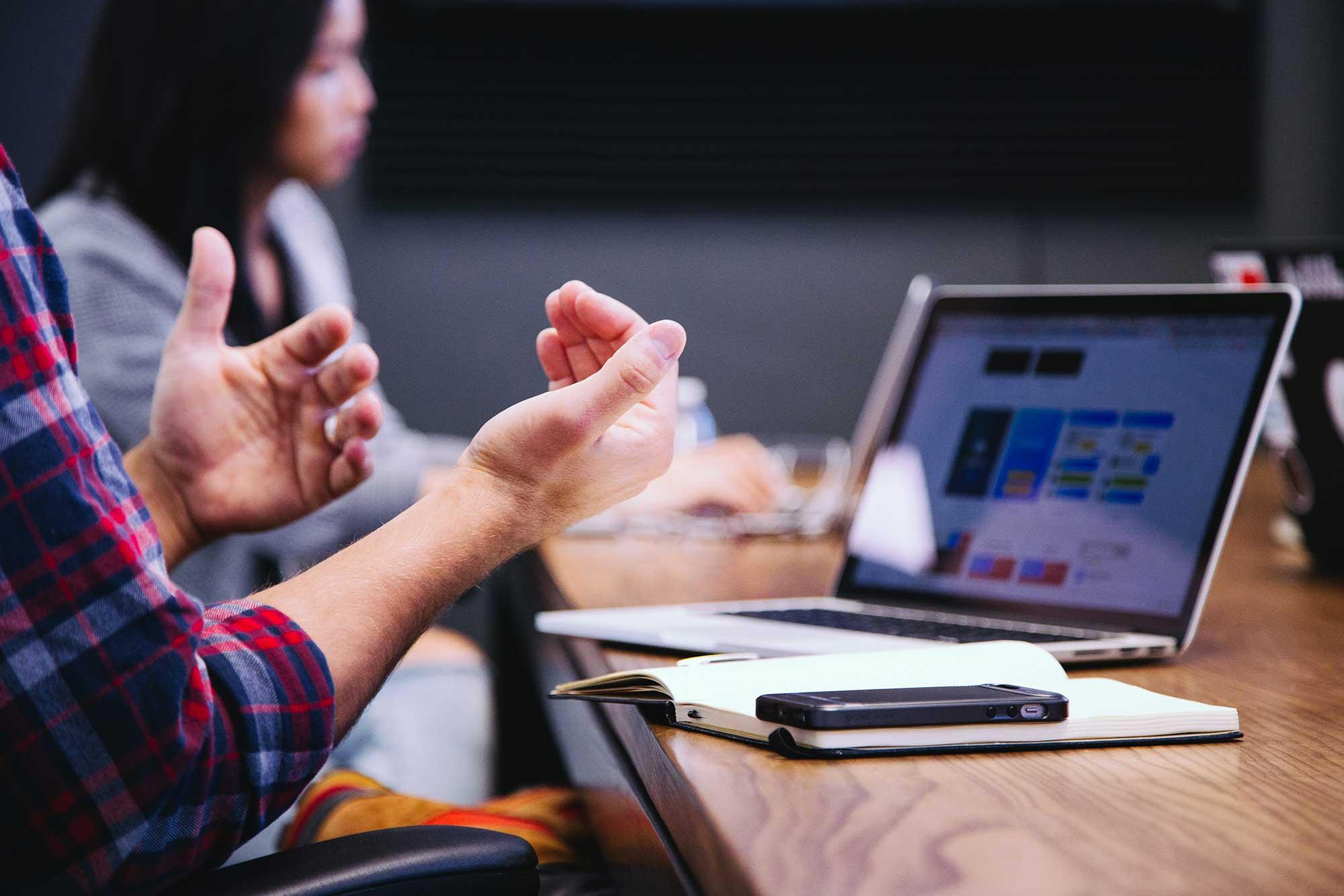 Explique avec ses mains devant un ordinateur, smartphone et cahier